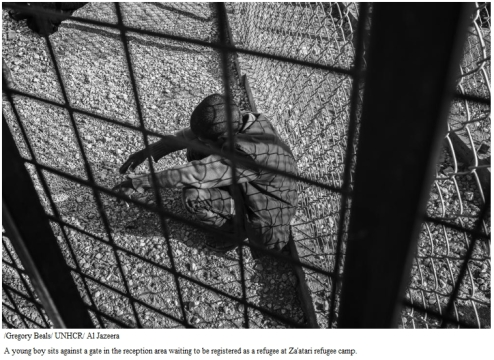 A young boy sits against a gate in the reception area waiting to be registered as a refugee at Za'atari refugee camp.