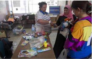 Rita handing out baby items, i.e., baby formula
